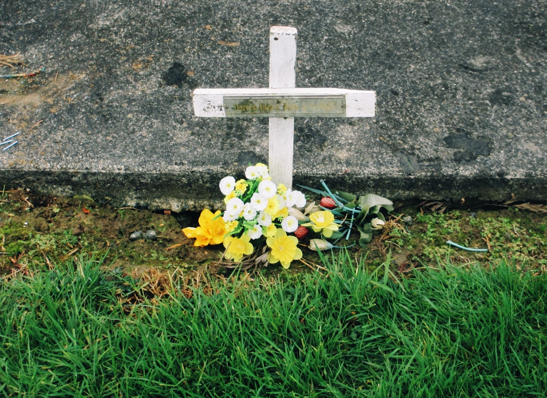 Photo of a grave site, featuring a white wooden cross and many flowers on it