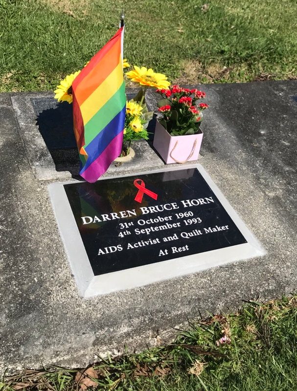 Grave stone, with a rainbow flag, and flowers beside it