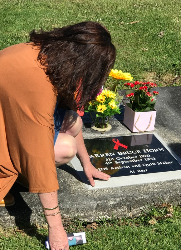 A woman sits near a grave stone with her hand on it