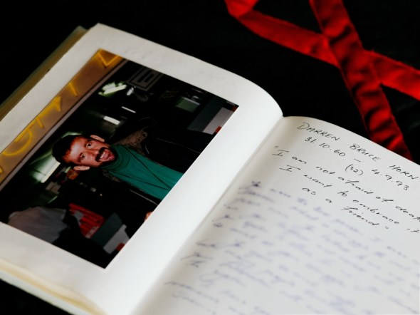 Photograph of an open diary. On the left page is a photograph of a man, on the right, a page of handwritten notes
