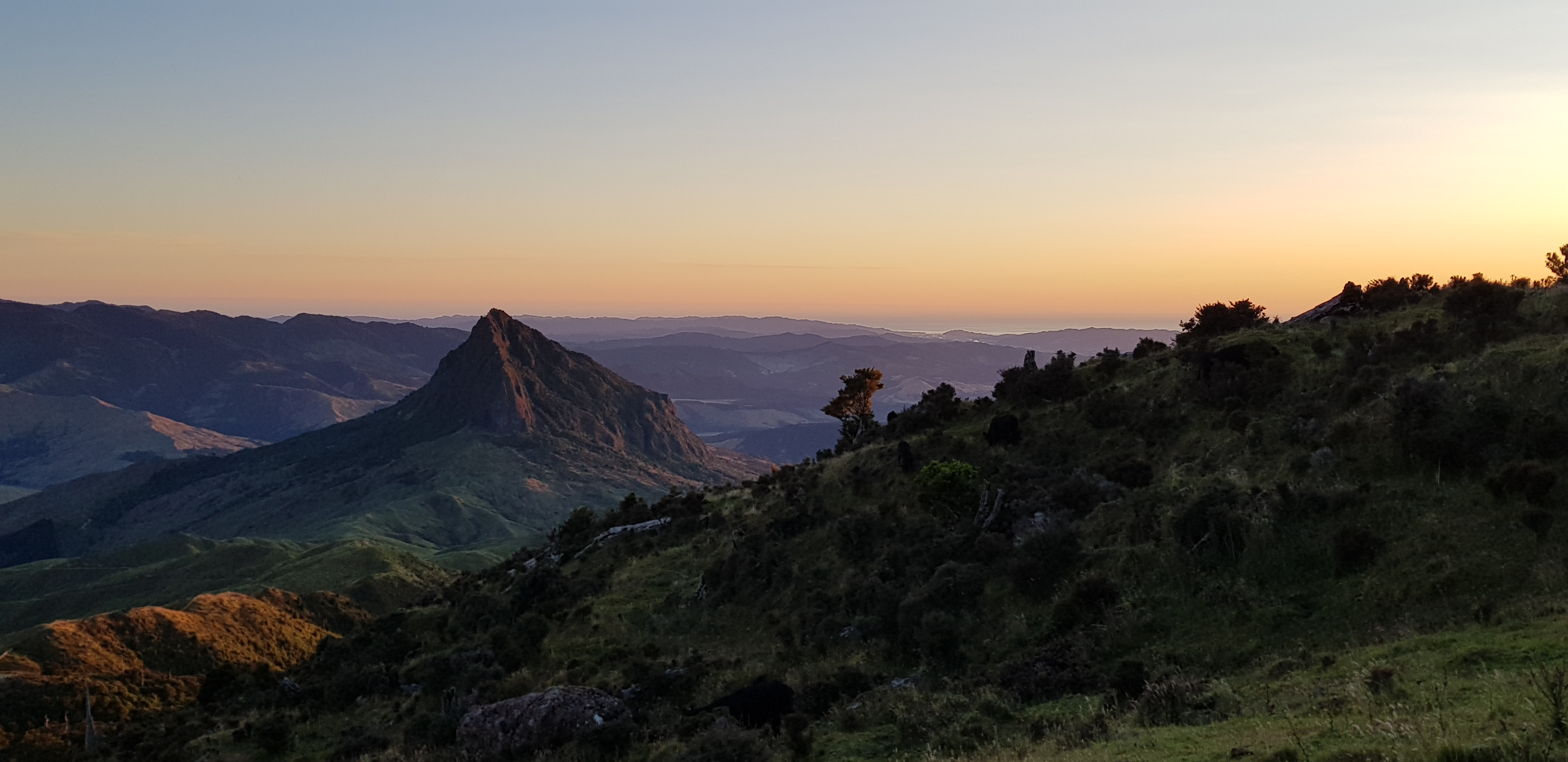A view of mountain ranges from the top of a mountain at sunset. There is a sharp, pointy mountain near the middle of the photo.