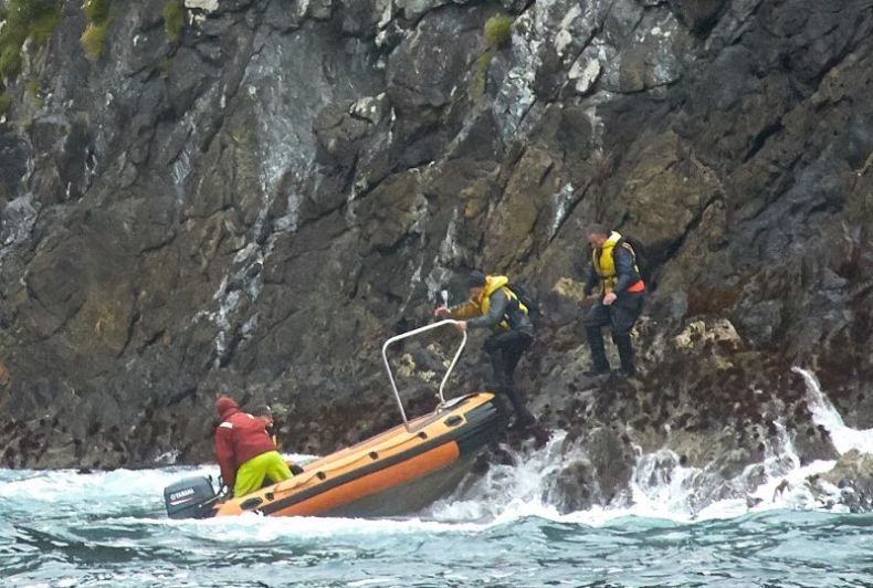 One man in wet-weather gear in an inflatable dingy close to rocks where two people in dark clothes and life jackets are standing.