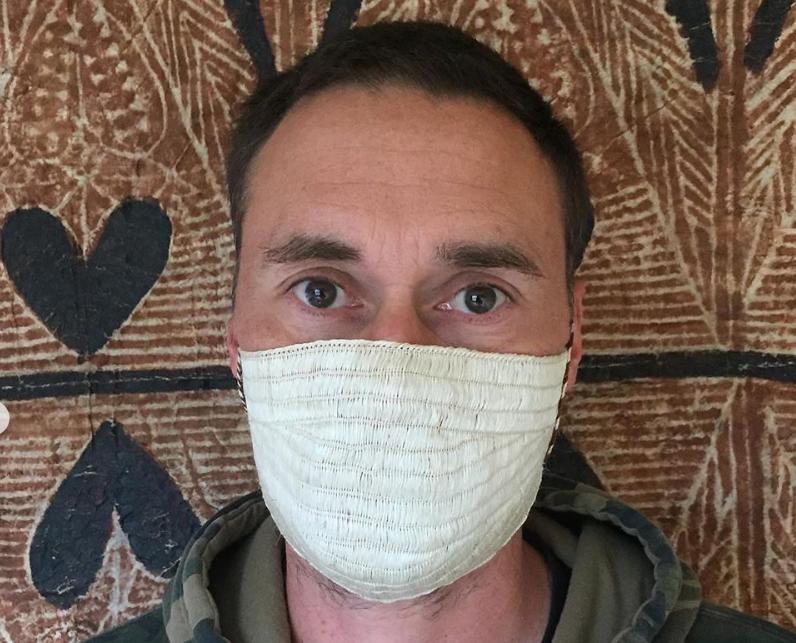 Close-up photo of a man wearing a mask made of muka (flax fibre)