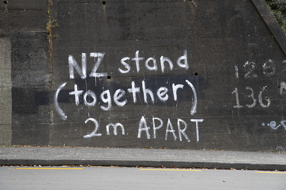 The words 'NZ stand together 2m apart' in white on a grey wall