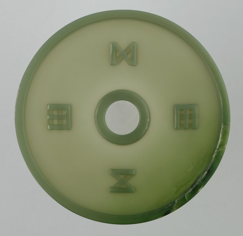 A circle of opaque pounamu shaped like a jade coin with a circle in the centre and four marking in a North, South, East, West layout