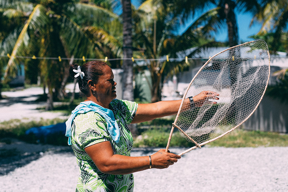 A woman holds a fishing net. Behind her is an empty washing line and several palm trees