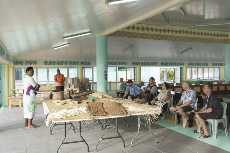 A group of people sits facing a table with multiple taonga (objects) on it