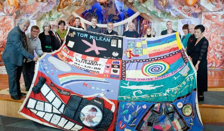 Thirteen people hold up a block from the New Zealand AIDS Memorial Quilt to face the camera, in Te Papa's marae