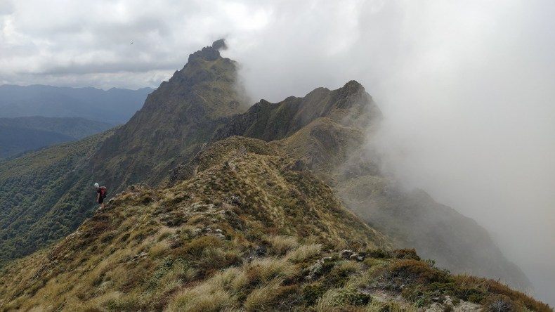 A person on the side of a sharp mountain ridge surrounded in mist