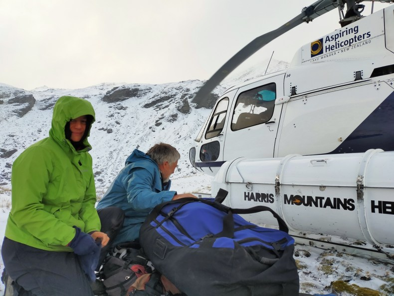 Heidi and David unloading our gear from the helicopter in the snowy Harris Mountains, Jan 2021. Photo by Antony Kusabs @ Te Papa.