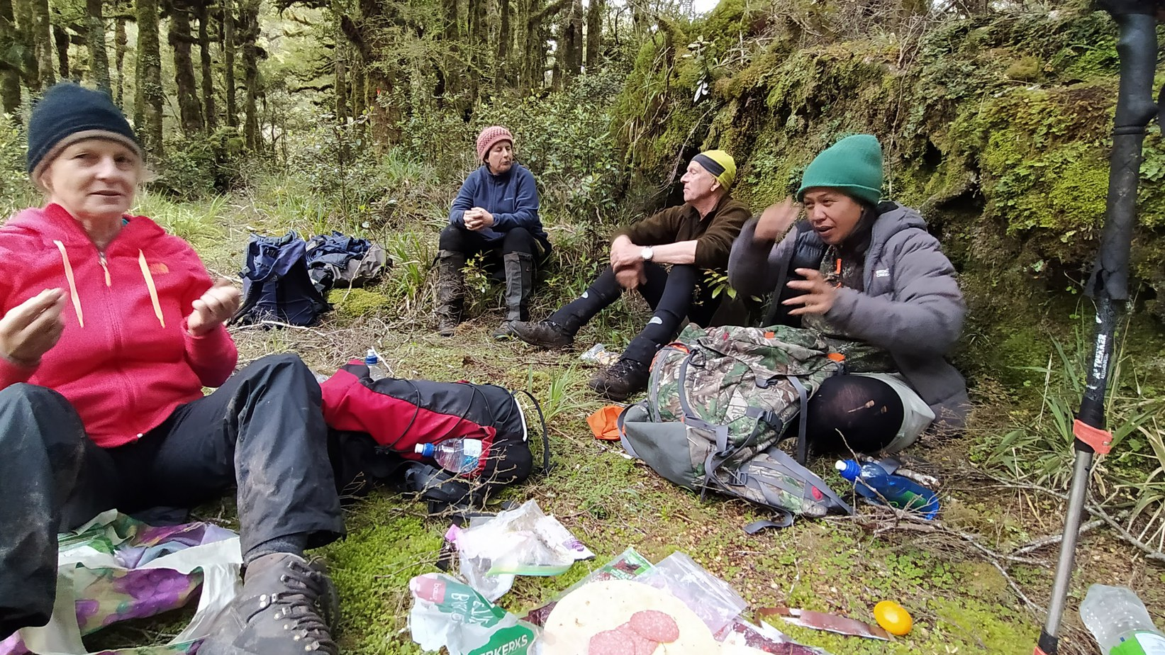 Four people with hiking gear on sitting in the bush having a picnic lunch