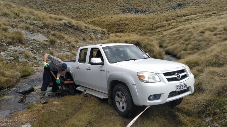 Ant Kusabs and David Lyttle attempting to get one of our 4WD vehicles out of the stream on a 4WD track in the Pisa Range, Jan 2021. Photo by Heidi Meudt, @ Te Papa.