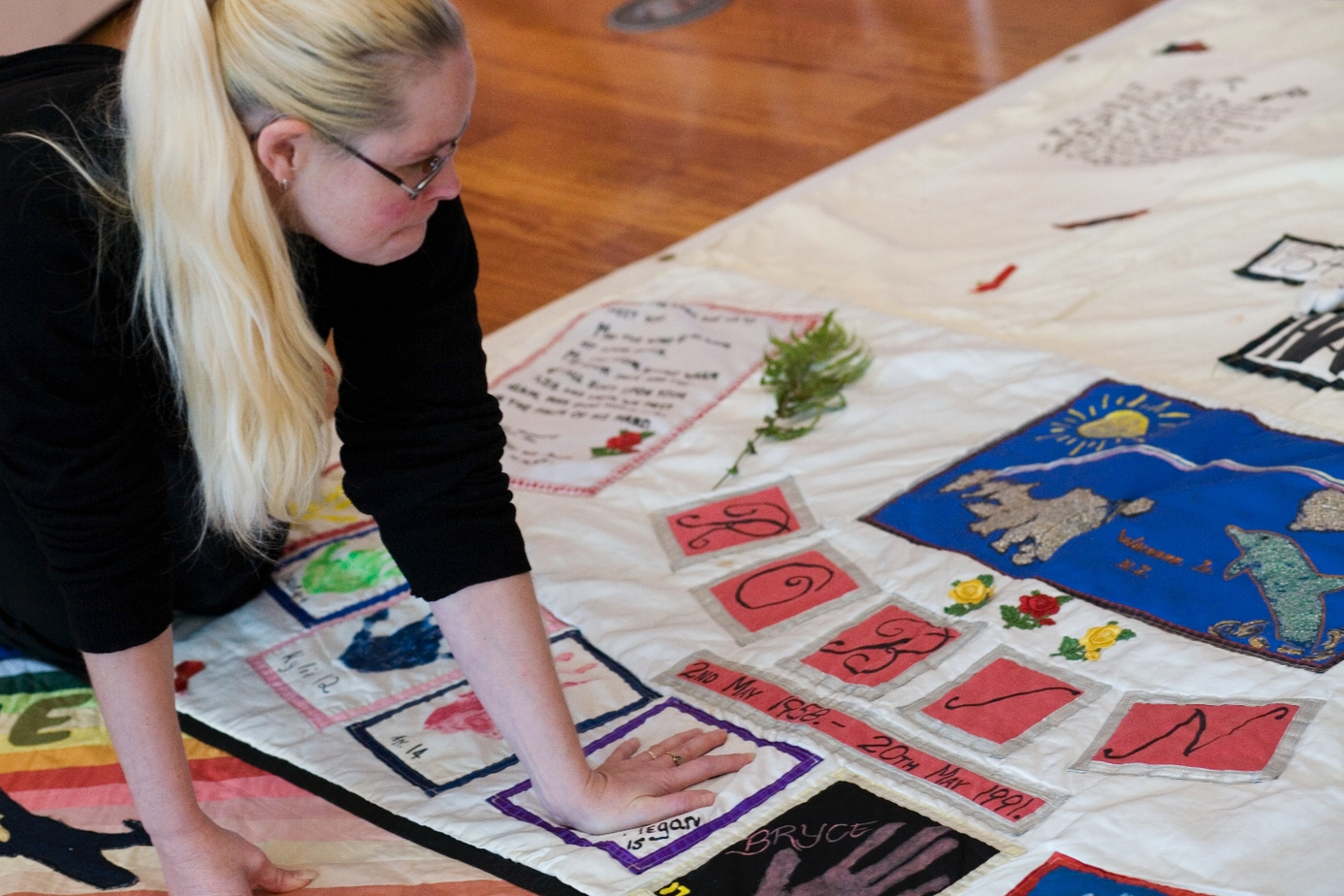 A woman places her hand on the part of a quilt that has an embroidered version of her hand on it