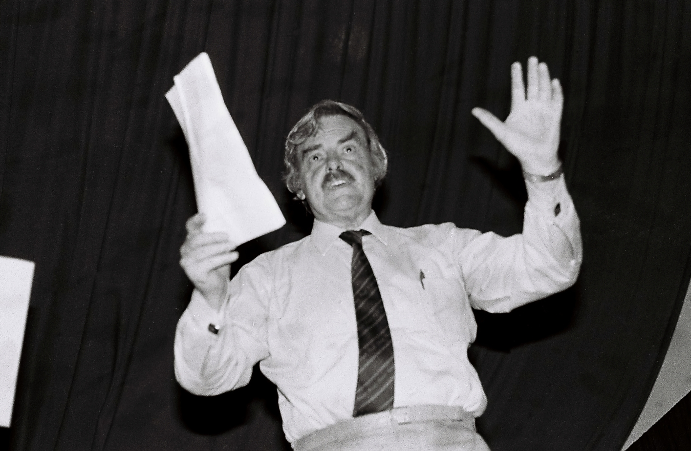 A man stands addressing an unseen crowd. He has his hands in the air – in one raised hand he holds a document. In his pocket is a pen and his tie is tucked into his pants