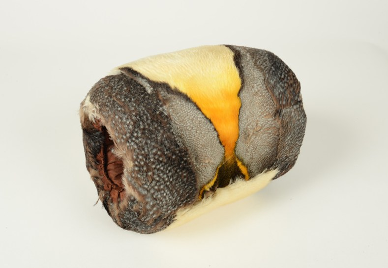 A muff for hands made with the skin of a king penguin sitting on a pale surface