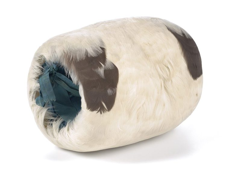 A white muff with brown and turquoise feathers sitting on a white surface