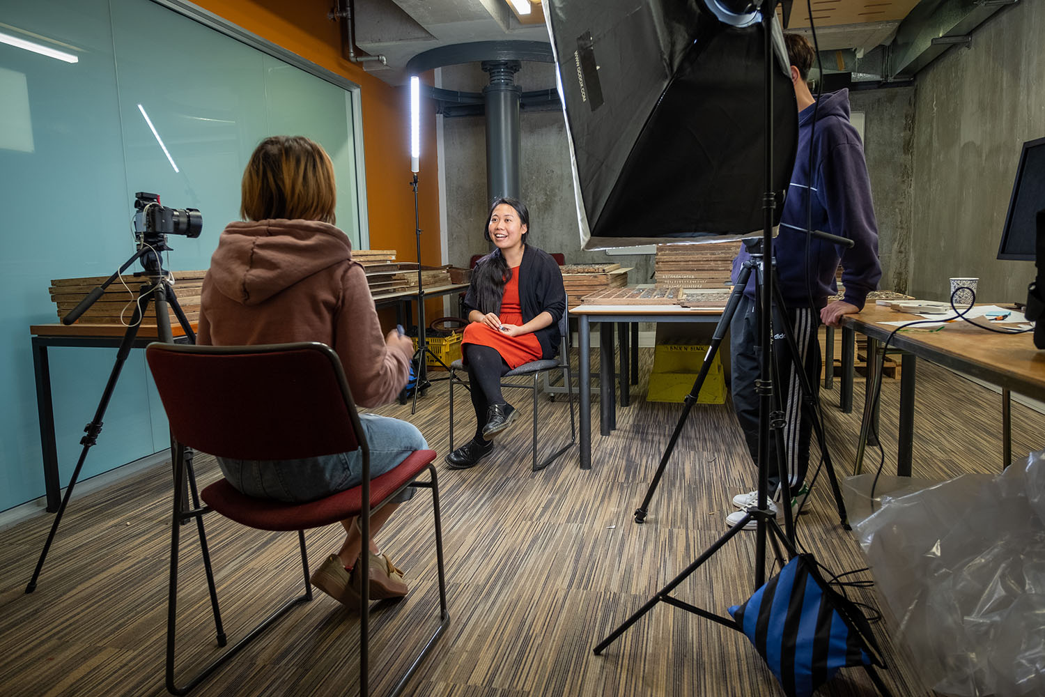 A woman sit on a chair in the middle of a room, being interviewed by another woman sitting opposite her. A large light shines on the subject