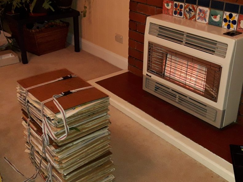 A stack of flat A4 sheets of paper and cardboard bound together with strops sitting in front of a gas heater.