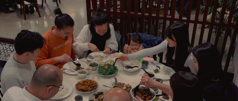 A group of people sit around a table in a restaurant eating food from shared plates in the middle
