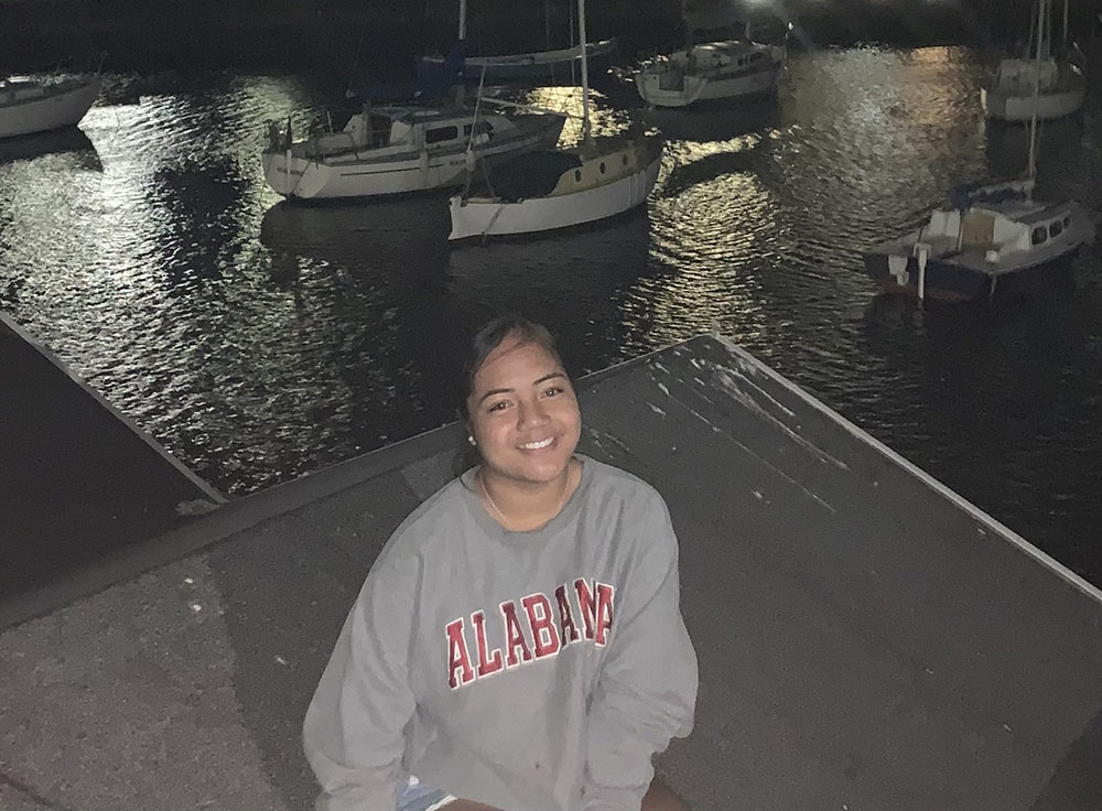 Young woman poses at night for a photo at a harbour with bots on the water in the background