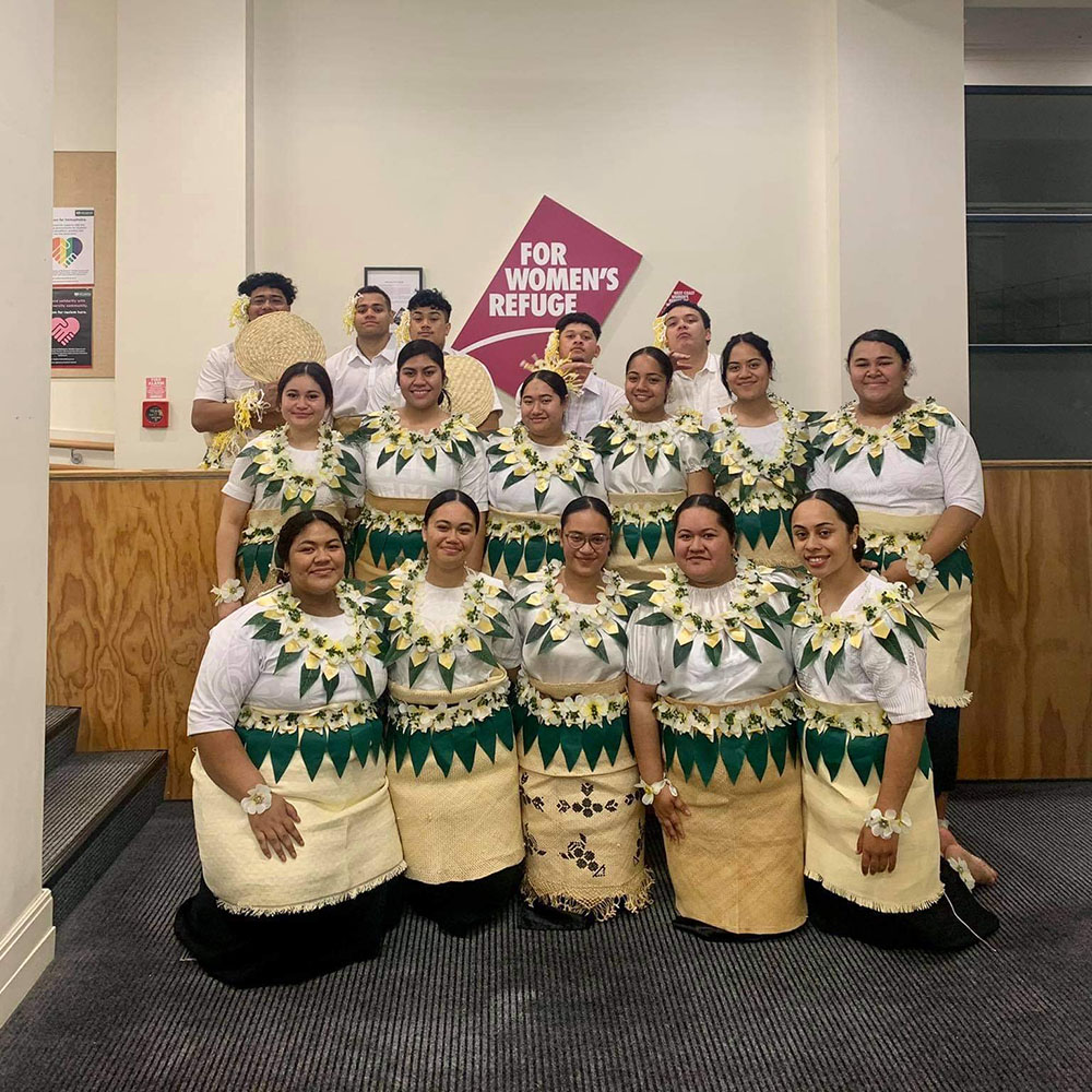 A group of 16 students in Tongan dress pose for a group photo