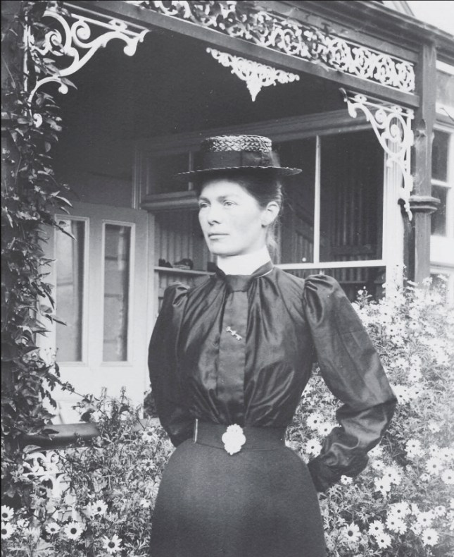 A black and white photo of a woman in dark victorian clothing and a hat standing in front of a wrought iron-framed verandah of a cottage that is surrounded by flowers.